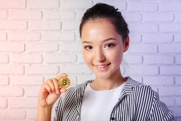 Женщина показывая золотую монетку биткойна. криптовалюта