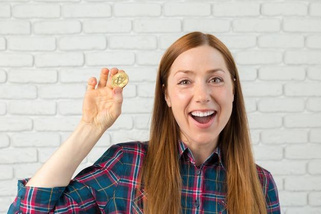 Женщина показывая золотую монету биткойна. криптовалюта