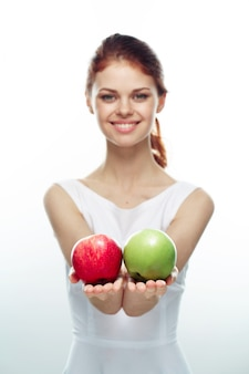 緑と赤のリンゴを示す女性
