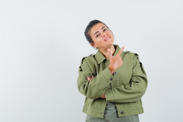 재킷, 티셔츠에 총 제스처를 보여주는 여자와 자신감을 찾고