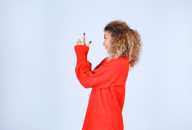 Женщина показывает пистолет знак в руке.