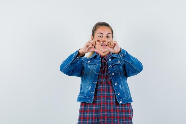 Donna che mostra il gesto del cuore in camicia, giacca e guardando allegro, vista frontale.
