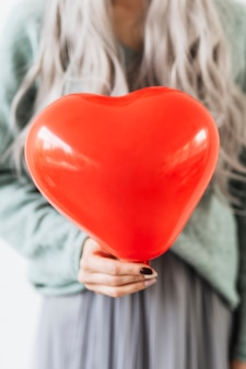 Woman showing a heart red balloon