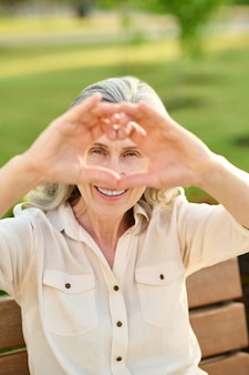 Woman showing heart with fingers outdoors