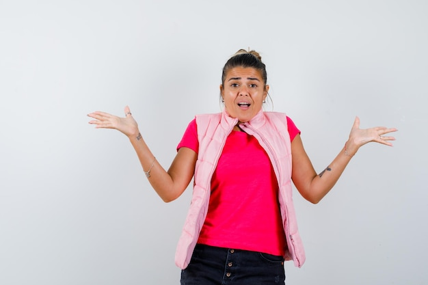 Tシャツ、ベストで無力なジェスチャーを示し、興奮しているように見える女性