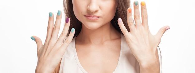 Женщина показывает свои цветные ногти на белом