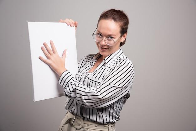 Donna che mostra la sua tela bianca vuota su sfondo grigio