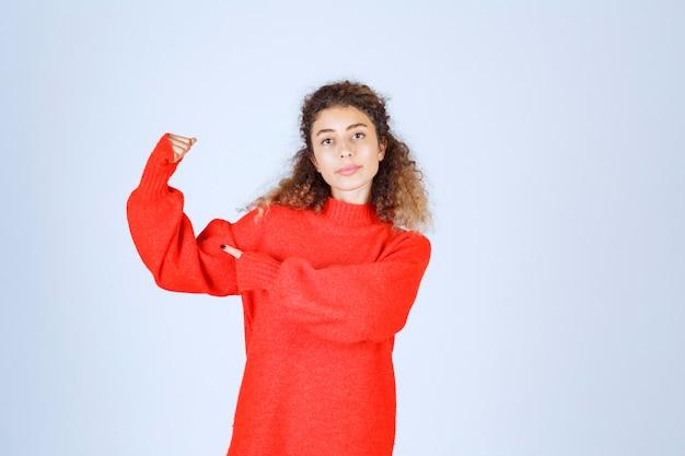 彼女のfostを示し、彼女の腕の筋肉を指している女性。