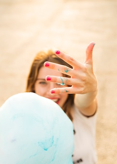 Woman showing her hand with blue candy floss