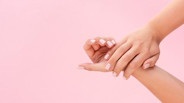 Woman showing her manicure on pink background with copy space