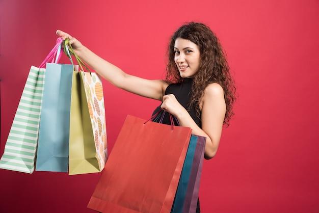 빨간색 배경에 그녀의 새로운 구매 옷을 보여주는 여자. 고품질 사진