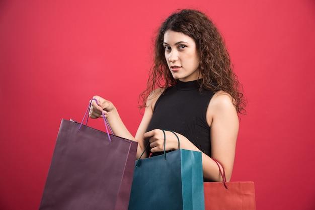 Женщина показывает ее новую одежду покупки на красном фоне. фото высокого качества