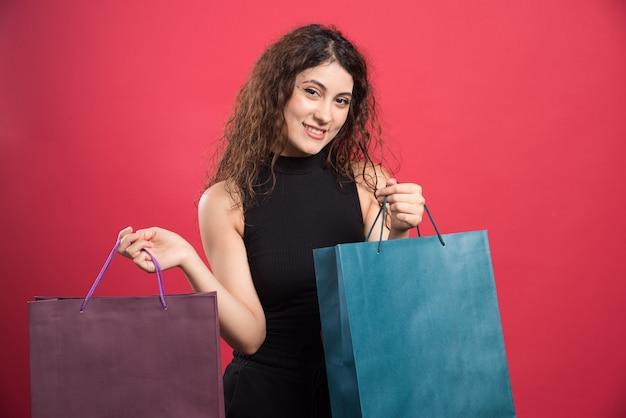 Donna che mostra i suoi nuovi vestiti di acquisto su sfondo rosso. foto di alta qualità