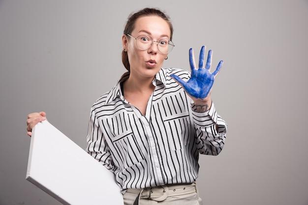 회색 배경에 그녀의 페인트 손을 보여주는 여자