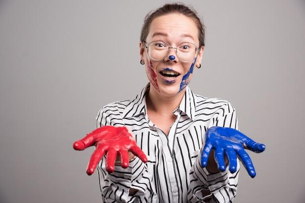 La donna che mostra le sue mani di vernici su sfondo grigio