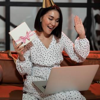 Женщина показывает свой подарок во время видеочата на новогодней вечеринке