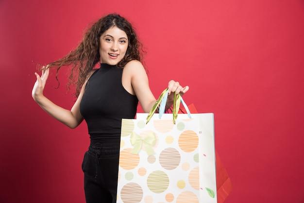 Женщина показывает свои покупки на красном фоне. фото высокого качества