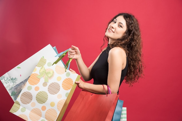 Woman showing her purchases on red background . high quality photo