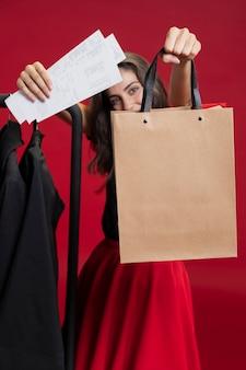 Donna che mostra i suoi sacchetti della spesa