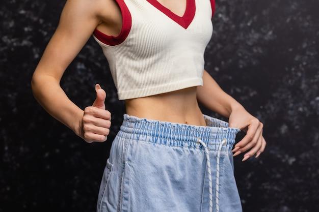 Женщина показывает, сколько веса она потеряла.