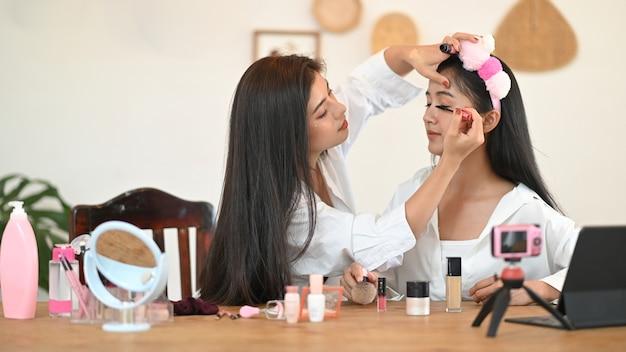 Женщина показывает, как наносить макияж через онлайн-видео