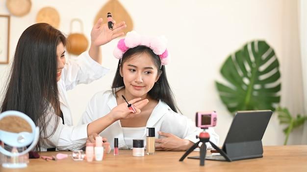 Женщина показывает, как наносить макияж через онлайн-видео Premium Фотографии