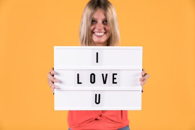 Woman showing i love you text on light box