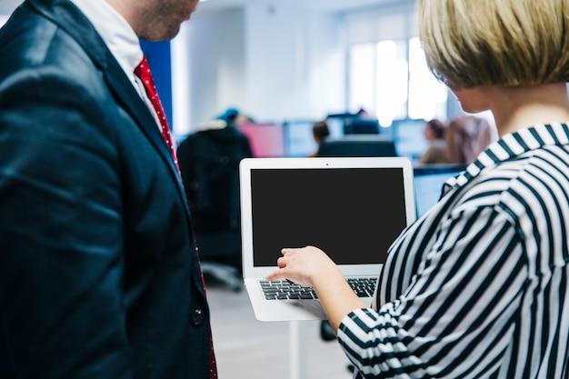 Donna che mostra il computer portatile al collega