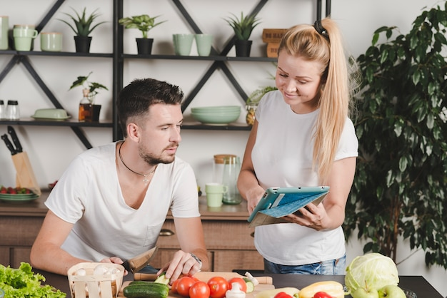 Woman showing laptop to man cutting vegetables