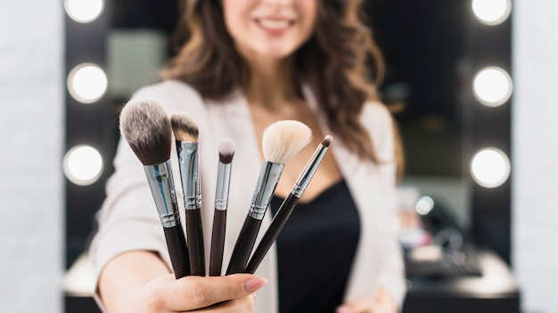 Woman showing makeup brushes on mirror background