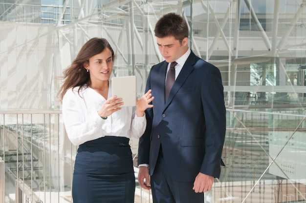 Woman showing man data on tablet, woman looking astonished
