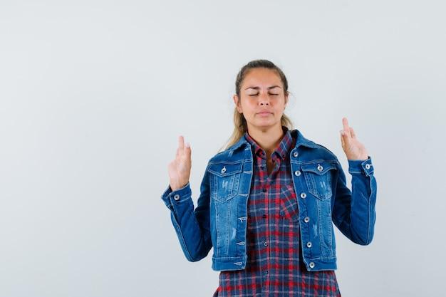 Женщина показывает жест медитации в рубашке, куртке и выглядит мирно, вид спереди.