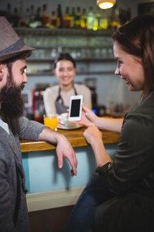 Donna che mostra il telefono mobile per l'uomo