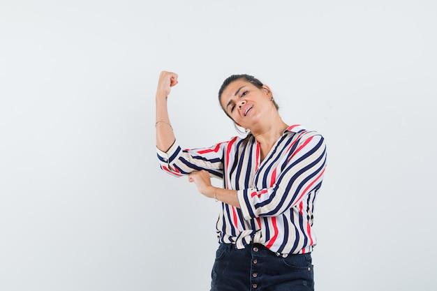 여자 셔츠, 치마 팔의 근육을 보여주는 자랑스럽게 찾고.