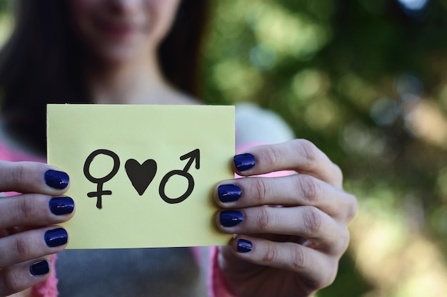 Woman showing a notepad, gender equality concept.
