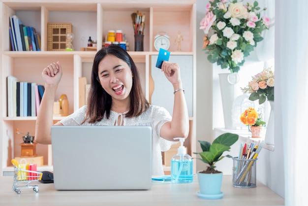 発生コロナウイルス病(covid-19)中に自己検疫のためのライフスタイルニューノーマルでオンラインショッピングした後の幸せを示す女性。