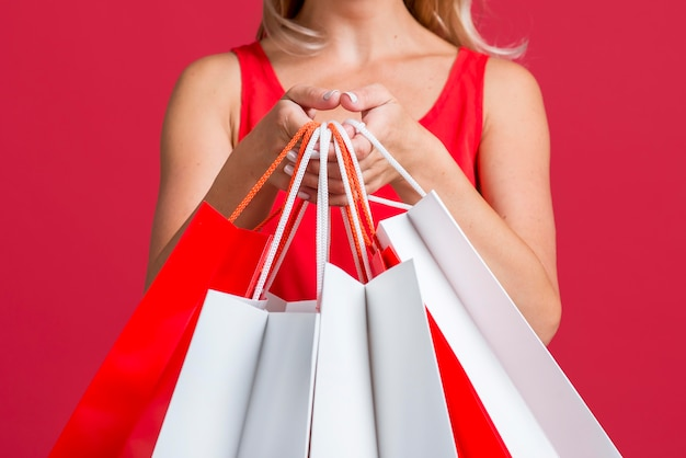 Woman showing off lots of shopping bags after shopping spree