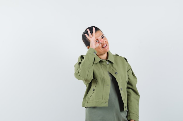 Женщина показывает хорошо жест на глаз в куртке, футболке и выглядит удачливым.