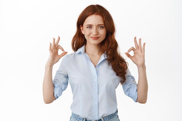 Женщина показывает жест ок с уверенным и напористым лицом, довольна хорошей вещью, хвалит выбор, стоит на белом