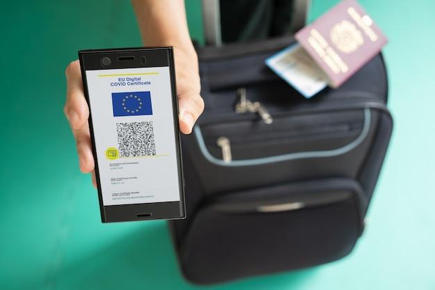Женщина показывает на смартфоне цифровой сертификат covid ес с четырехъядерным кодом