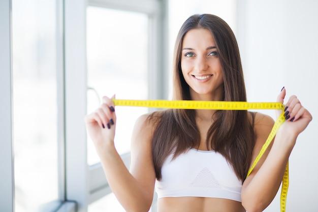 彼女がどれだけ体重を減らしたかをテープで示す女性