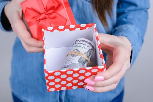 고립 된 돈을 번들 오픈 giftbox를 보여주는 여자