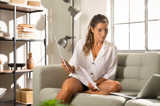 Donna che mostra documenti al computer portatile