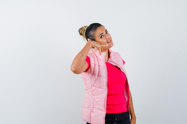 Donna che mostra il gesto del telefono in maglietta, gilet e sembra sicura
