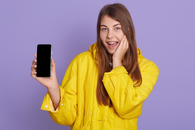 誰かに電話の画面を見せている女性は興奮しているように見え、薄紫色の壁の上に孤立したポーズで黄色のシャツを着ている間幸せな笑顔を見せています。