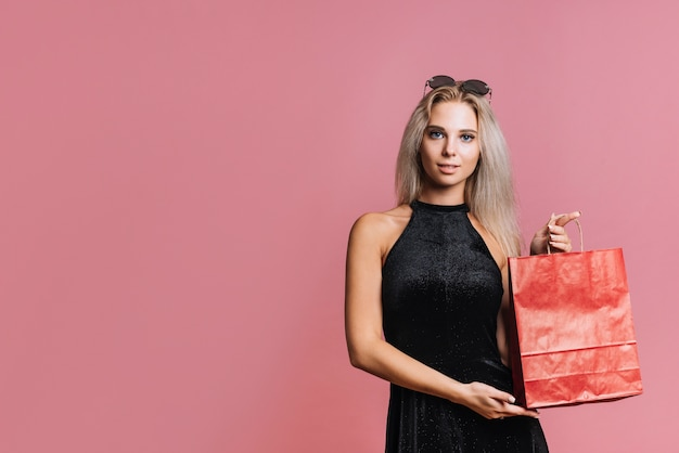 Woman showing red paper bag