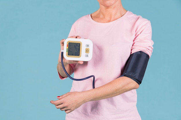Woman showing results of blood pressure on electric tonometer screen