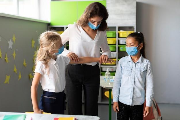 Donna che mostra la giusta distanza sociale ai bambini
