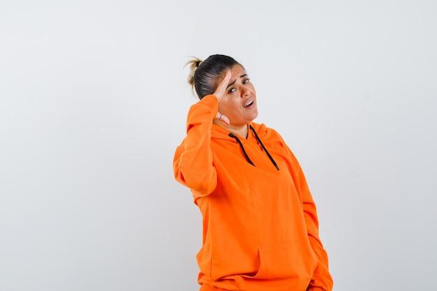 Женщина показывает жест салюта в оранжевой толстовке с капюшоном и выглядит уверенно