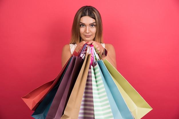 빨간 벽에 중립 표정으로 쇼핑백을 보여주는 여자.